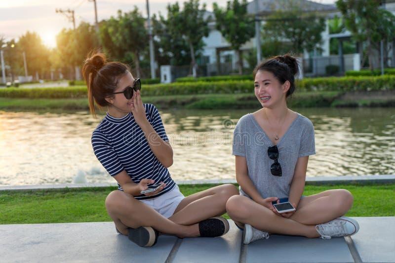 谈和笑闲话的愉快的妇女朋友拿着手机在公园户外有绿色背景 两年轻亚洲人 库存照片