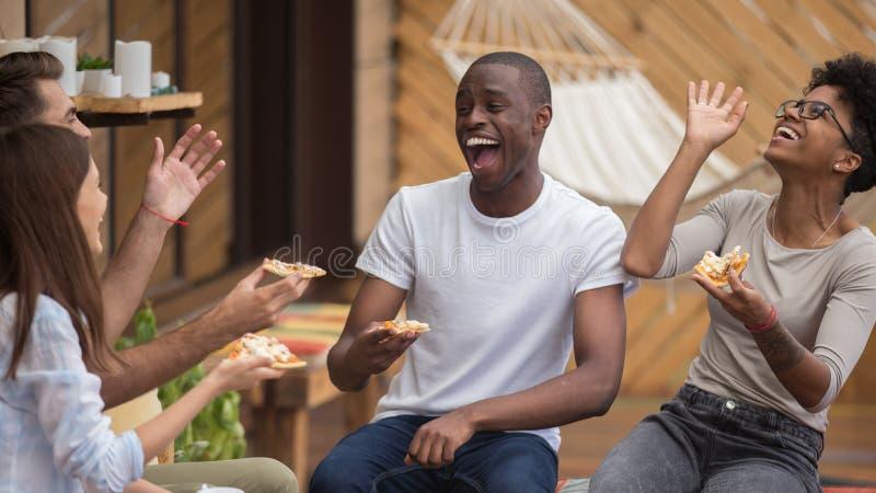 谈愉快的不同的朋友笑分享在咖啡馆的晚餐 免版税库存图片