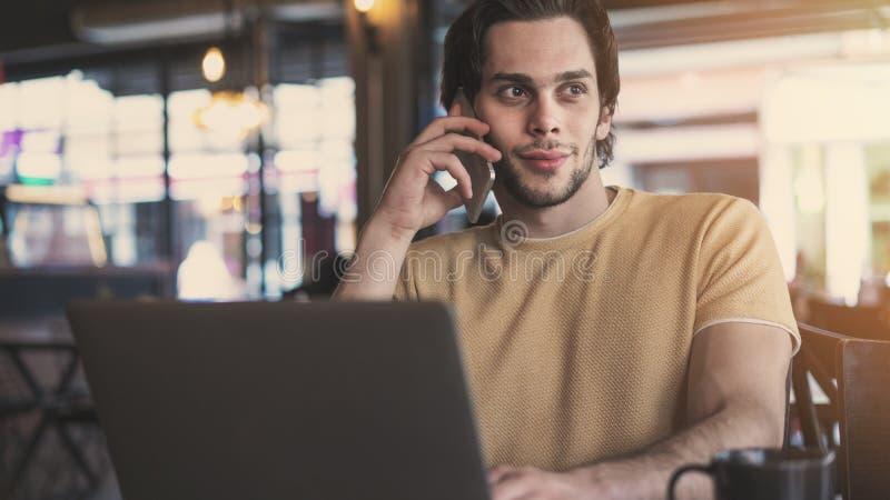 谈手机和使用手提电脑的年轻人在咖啡馆 免版税库存图片