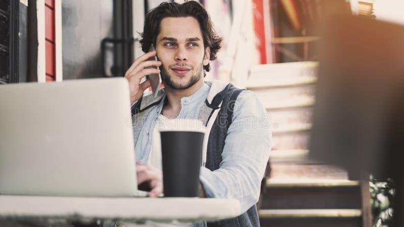 谈手机和使用手提电脑的年轻人在咖啡馆 库存图片
