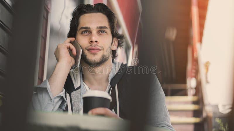 谈的年轻人在咖啡馆的手机 免版税库存照片