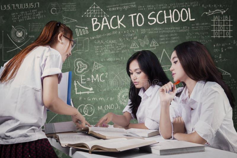 谈论三名的学生schoolwork 免版税库存照片