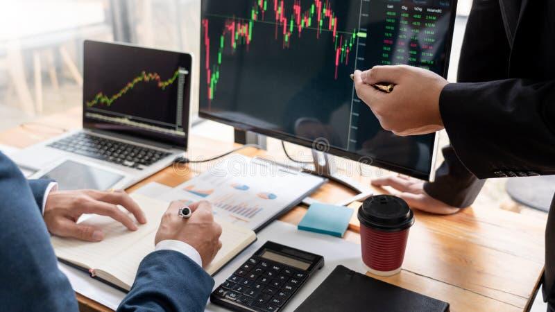 谈论与显示屏分析数据、股票市场贸易的图表和报告投资的股票经纪人队 免版税库存图片