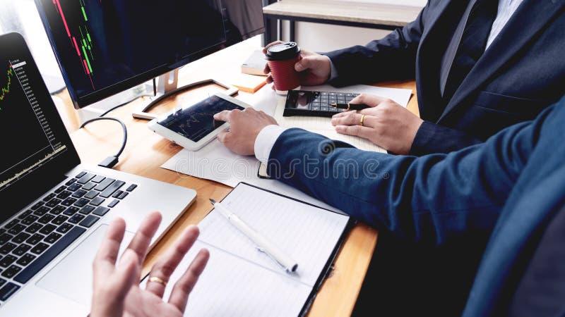 谈论与显示屏分析数据、股票市场贸易的图表和报告投资的股票经纪人队 免版税图库摄影