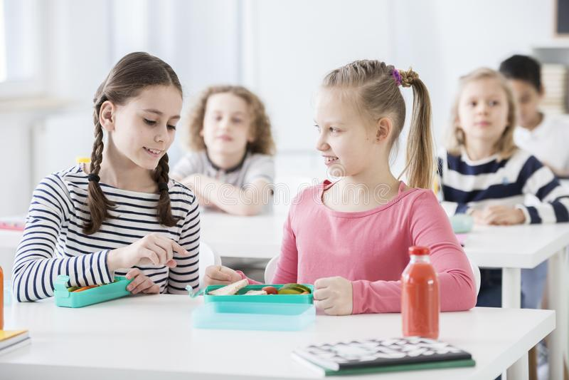 谈论与朋友的女孩健康食物在早餐断裂期间在学校 免版税库存图片