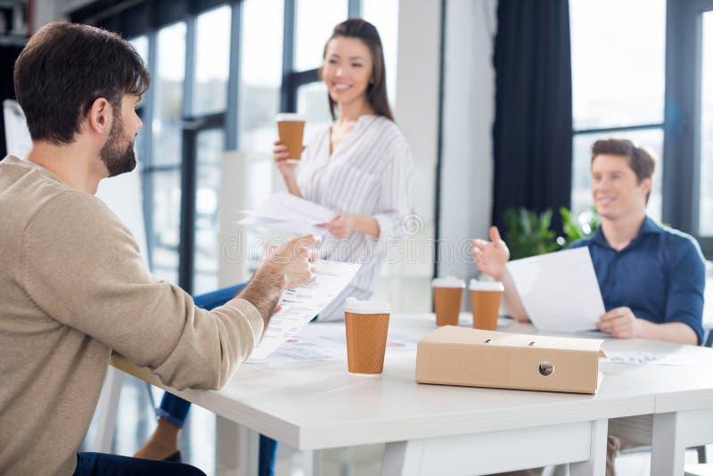 谈论专业年轻的买卖人喝从纸杯的咖啡和纸 免版税库存图片