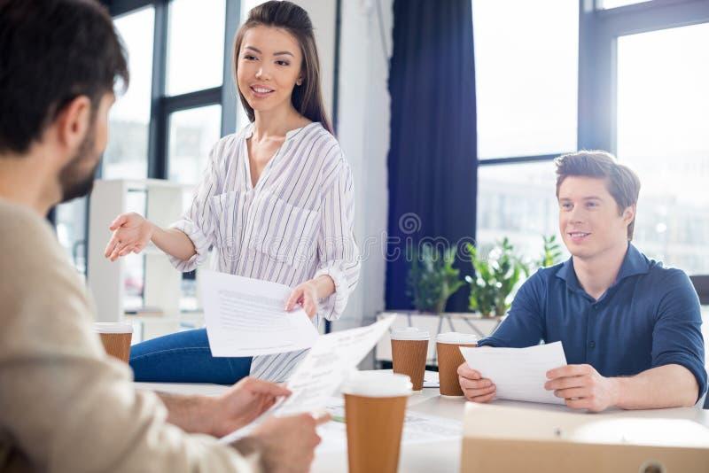 谈论专业年轻的买卖人喝从纸杯的咖啡和纸 免版税库存照片