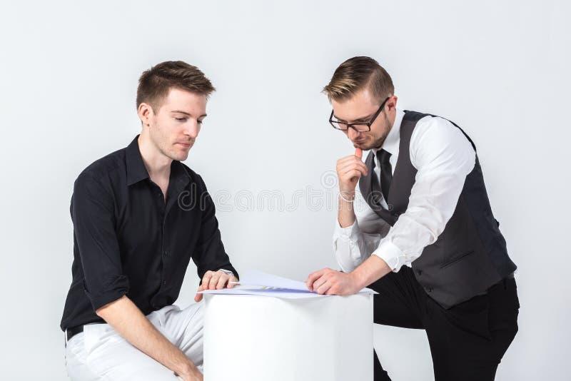 谈论两个的商人坐和看事务的任务 免版税库存图片