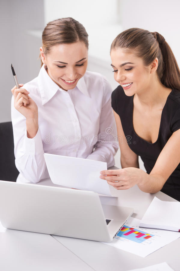 谈论两个年轻女商人或的办公室工作者文书工作 库存图片