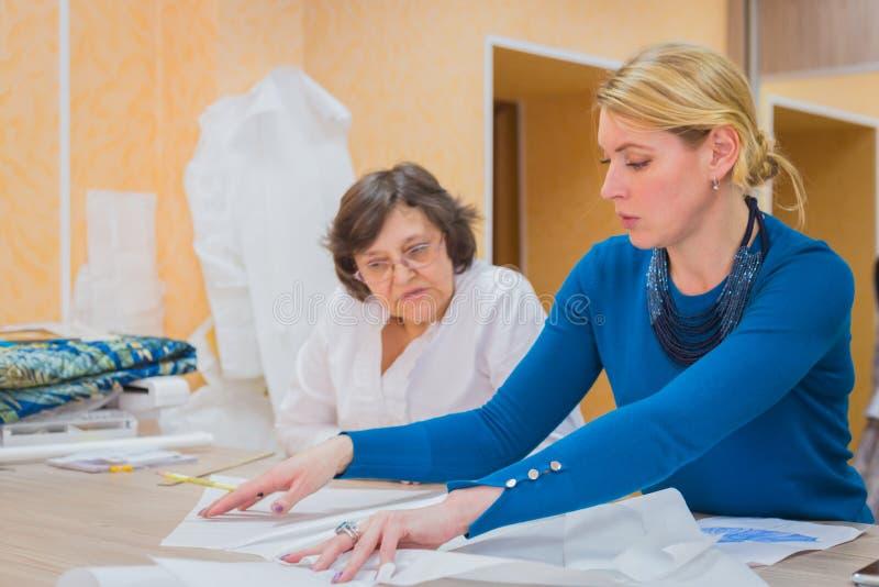 谈论两位的裁缝新的礼服的样式 免版税库存照片