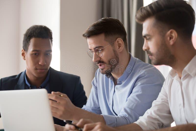 谈论严肃的男性的同事使用膝上型计算机企业想法 库存图片
