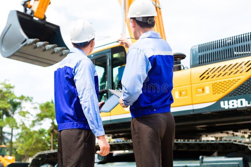 谈论亚裔的工程师在建造场所的计划 图库摄影