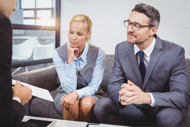 谈论企业的专家,当坐沙发时 免版税库存照片