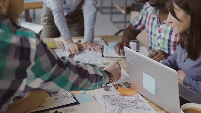 谈论创造性的企业的队建筑项目 混合的族种人激发灵感在时髦办公室 库存照片