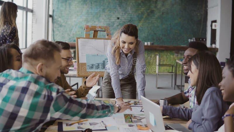 谈论创造性的企业的队建筑项目 混合的族种人激发灵感在时髦办公室 免版税库存照片