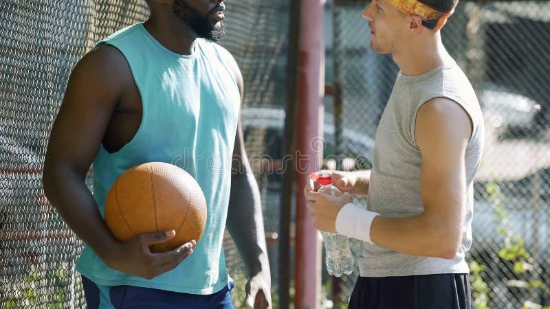 谈论前个比赛比分的肌肉篮球运动员在体育场,体育 免版税库存照片