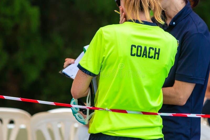 谈论后面观点的两位女性体育游泳的教练 免版税库存图片
