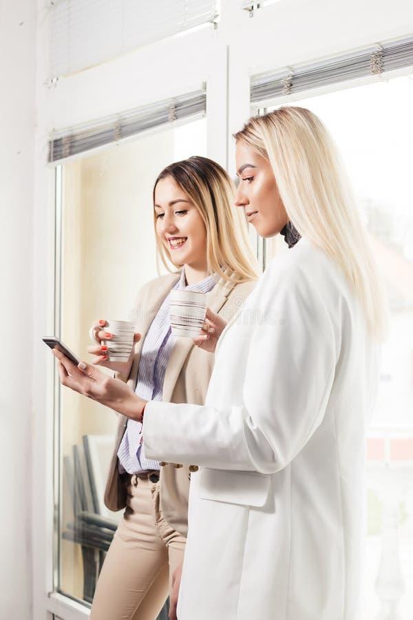 谈论和使用电话的两个女性同事 库存图片
