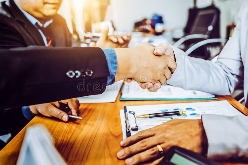 谈论商务伙伴的同事在现代办公室握手在见面的管理项目 库存照片