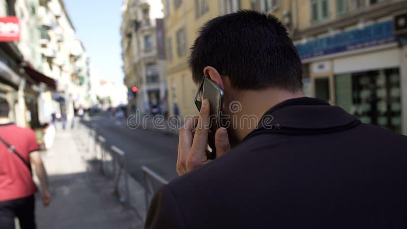 谈论在电话的问题和走城市街道,技术的商人 免版税库存照片