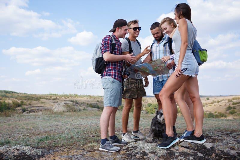 谈论小组的朋友看地图和户外 朋友努力去做在远足,森林,休闲,爱活跃生活方式 库存图片