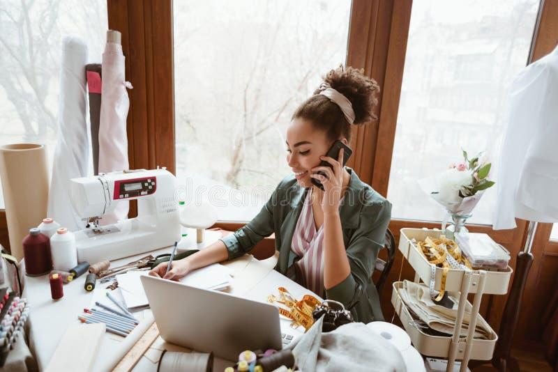 谈论年轻女人的设计师新的项目 设备最近的缝合的妇女年轻人 库存图片