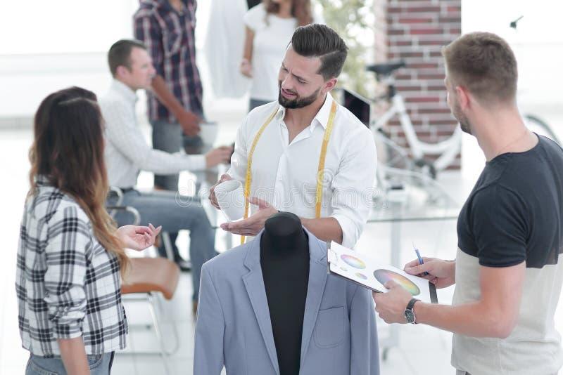 谈论年轻的设计师男性服装 免版税图库摄影