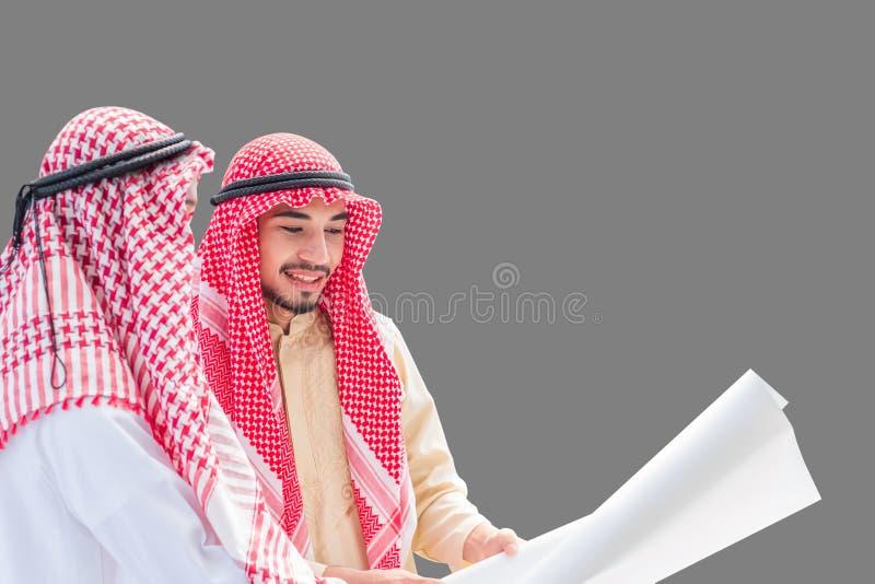 谈论建筑工作的阿拉伯工程师画象和核实与承诺的图纸到在被隔绝的灰色的成功 库存图片