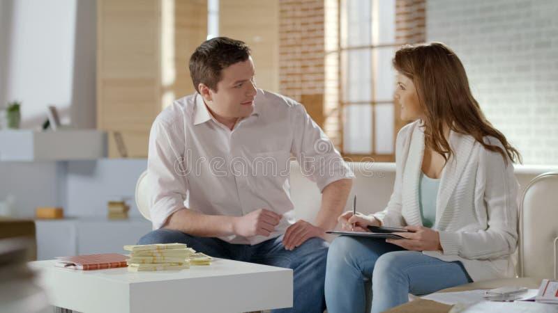 谈论愉快的富有的夫妇营业利润,美元的大总和在桌上的 免版税库存图片