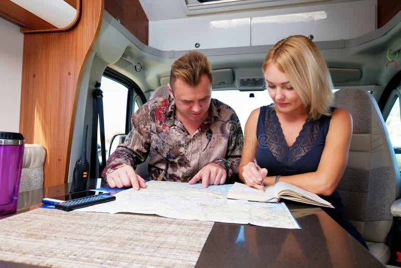 谈论未来冒险计划路线的夫妇看地图 免版税图库摄影