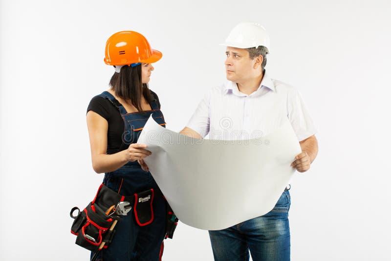 谈论男性建筑师和建造者的妇女画象建立计划 拿着卷轴式记录纸的工头 免版税图库摄影