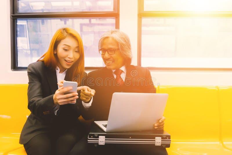 谈论画象两亚裔的买卖人和和工作忙个不停在火车 免版税图库摄影