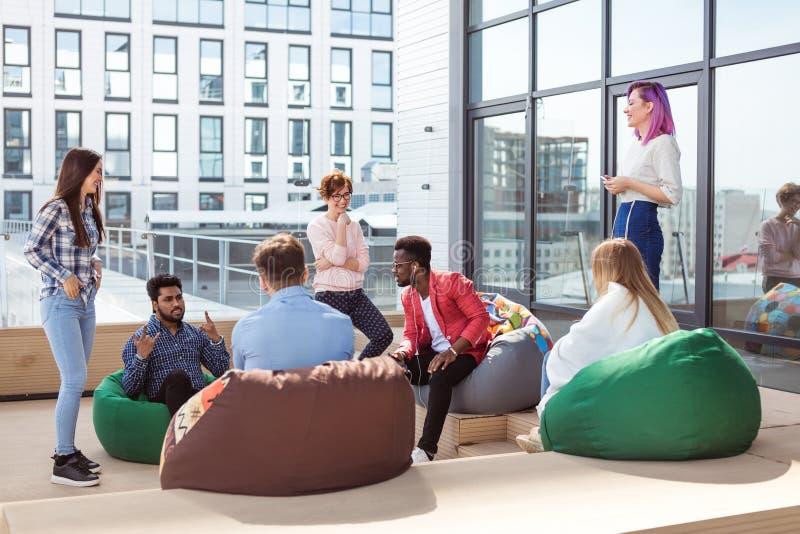 谈论的人们工作过程,当坐在室外时办公室的休息室 库存照片
