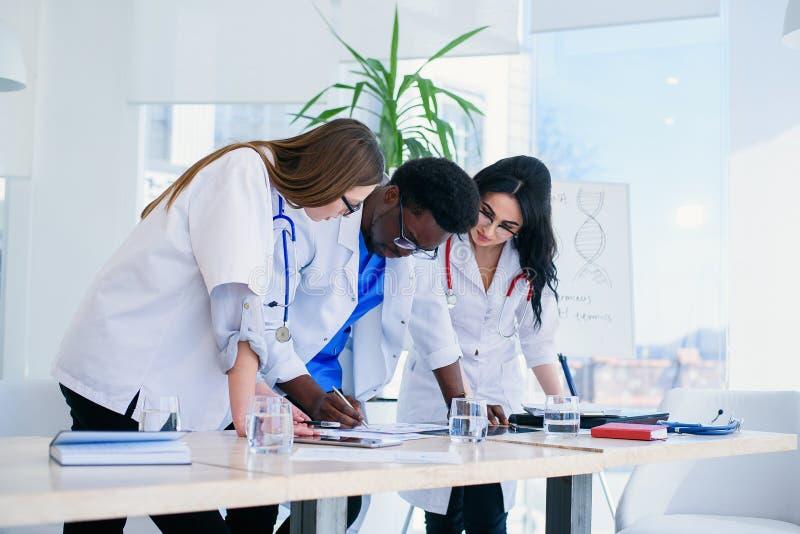谈论的医生的职业球队耐心X-射线结果 多族群医科学生谈论患者 免版税库存照片