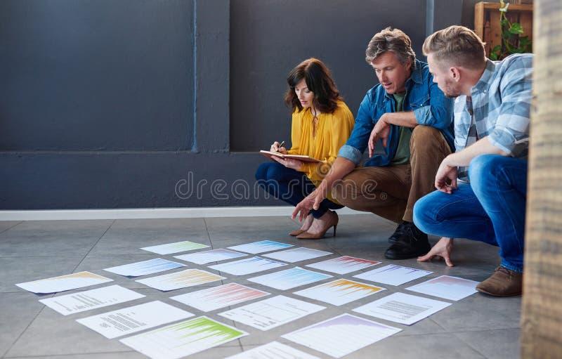 谈论的同事在一个现代办公室地板上计划的文书工作 免版税库存照片