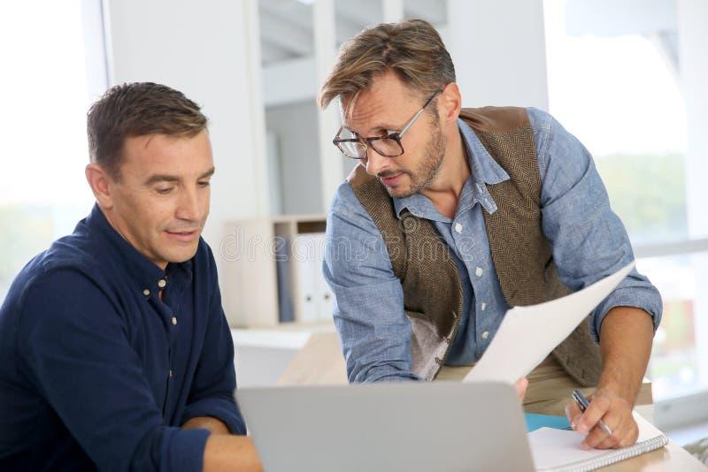 谈论的商人在办公室战略 免版税库存照片