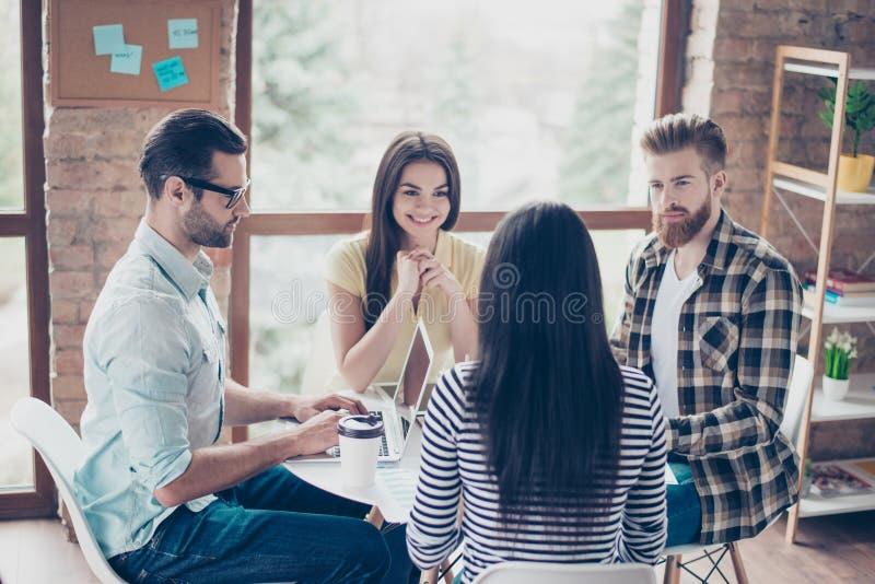 谈论的学生开会议在咖啡馆和最新的新闻 在spacy的工作站工作场所的俏丽的人民 免版税图库摄影