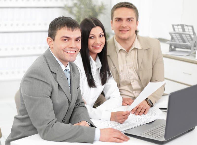 谈论的雇员坐在他们的书桌的财政图 免版税库存照片