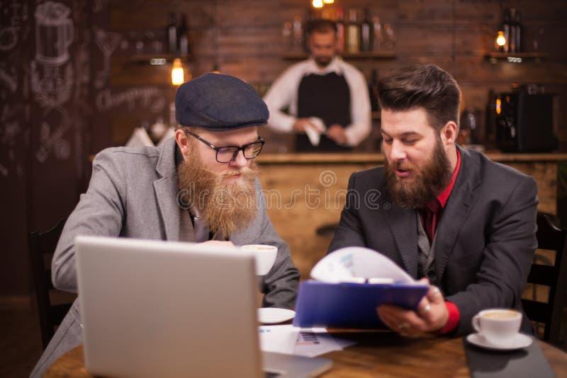 谈论财务的可爱的商人在他们的会议期间在coffeee商店 免版税库存照片