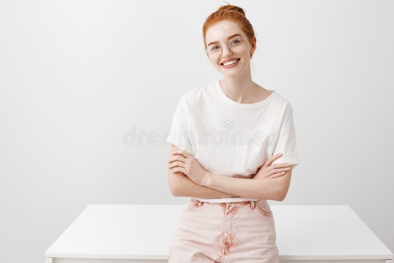 谈论迷人的工友新的项目 在玻璃和时兴的牛仔裤的有吸引力的女性红头发人,倾斜在桌 免版税库存照片