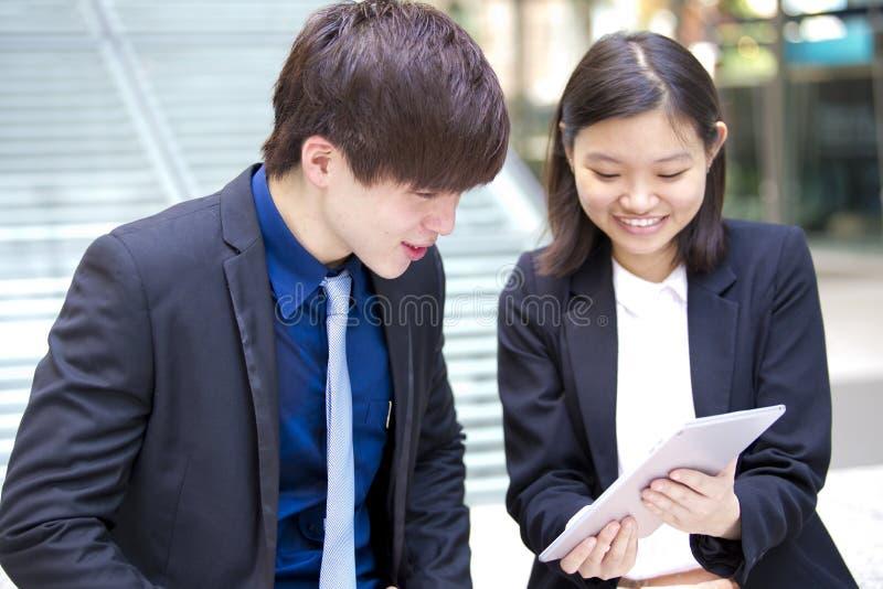 谈论年轻亚裔的商业主管使用片剂个人计算机 免版税库存照片