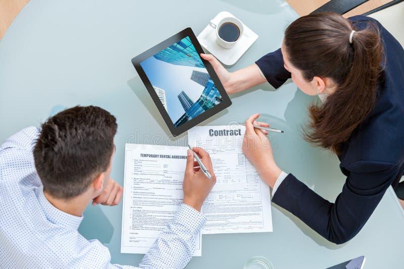 谈论年轻企业的夫妇租赁协议 免版税库存图片