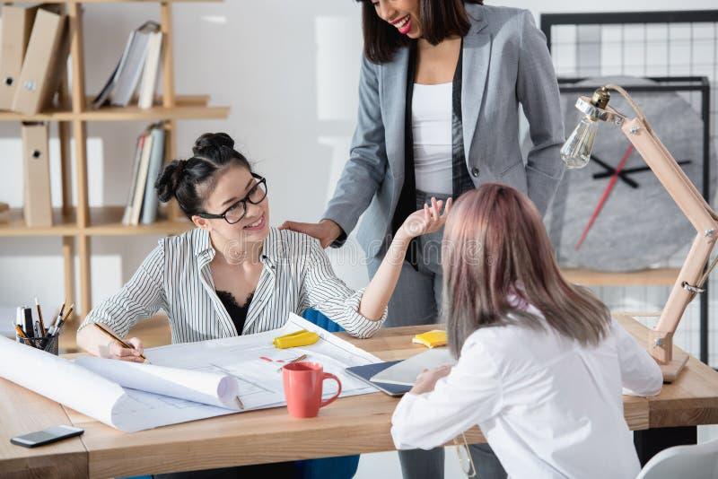 谈论年轻的女实业家与图纸一起使用和新的项目 库存图片