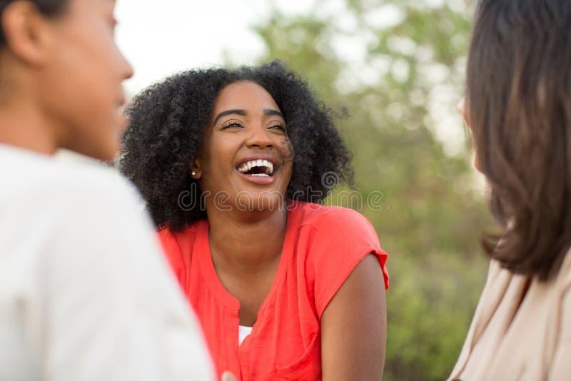 谈话不同种族的小组的妇女笑和 图库摄影