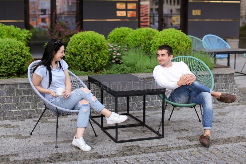 谈话与丈夫在街道咖啡馆和坐在椅子的妻子 免版税库存图片