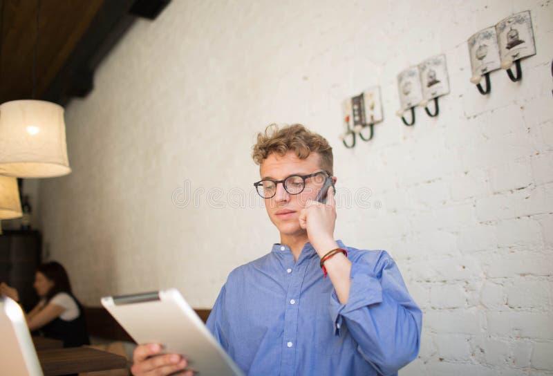 谈话与手机的客户和读财务新闻的成功的年轻商人在触摸板 免版税库存照片