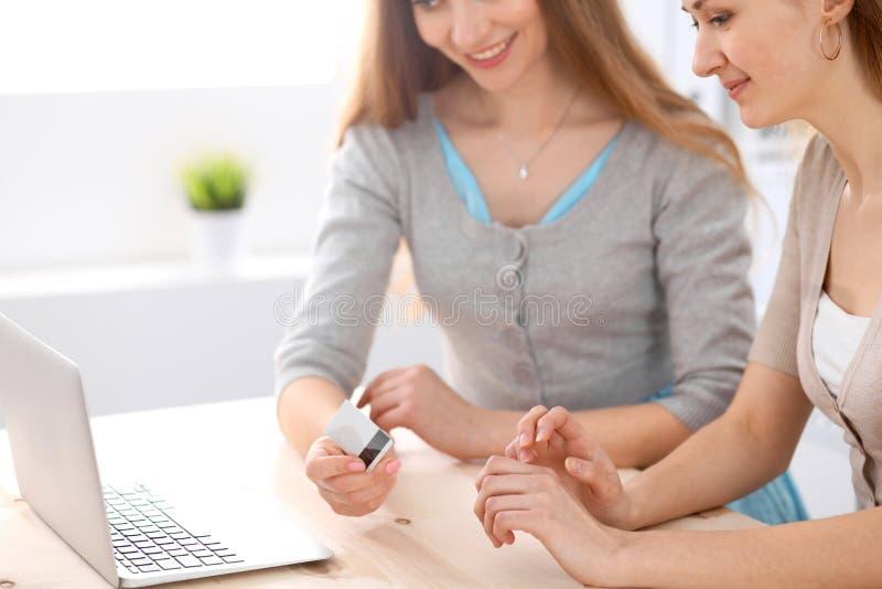 谈话两个的朋友或的姐妹采取交谈在与膝上型计算机的桌上 库存图片