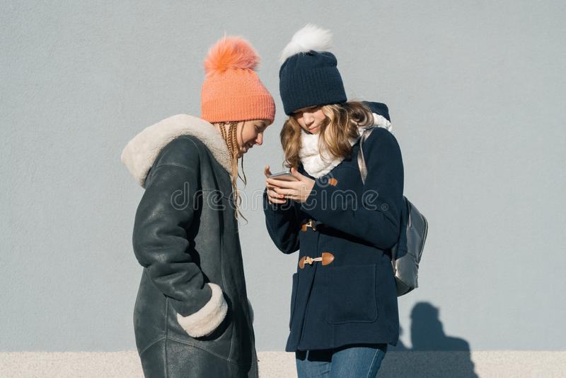 谈话两名十几岁的女孩的学生特写镜头室外冬天画象外形的微笑和,看手机的女孩 免版税库存照片