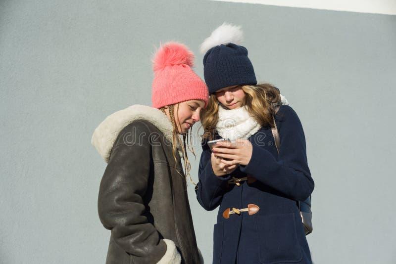 谈话两名十几岁的女孩的学生特写镜头室外冬天画象外形的微笑和,看手机的女孩 库存图片