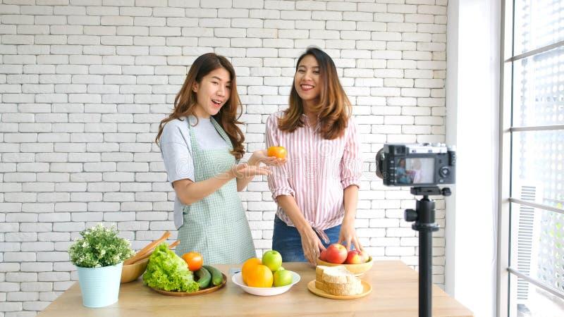 谈话两年轻亚裔妇女食物的博客作者,当记录有愉快的片刻、vlog概念、人民和技术的时录影 图库摄影